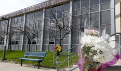 A bouquet of flowers is taped to a stairway rail near the closed entrance to Franklin Regional High School near Pittsburgh, on Thursday, April 10, 2014 in Murrysville, Pa. A knife wielding student injured over 20 people in a stabbing attack there on April 9. (AP Photo/Keith Srakocic)