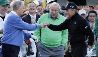 Arnold Palmer, center, watches as Jack Nicklaus, left, and Gary Player touch fists after Palmer hit his ceremonial drive on the first tee during the first round of the Masters golf tournament Thursday, April 10, 2014, in Augusta, Ga. (AP Photo/David J. Phillip)