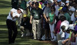 Spectators watch as Phil Mickelson hits out of the rough on the second fairway during the second round of the Masters golf tournament Friday, April 11, 2014, in Augusta, Ga. (AP Photo/Chris Carlson)