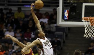 Milwaukee Bucks' John Henson (31) puts up a shot against Cleveland Cavaliers' Jarrett Jack, left, during the first half of an NBA basketball game Friday, April 11, 2014, in Milwaukee. (AP Photo/Jeffrey Phelps)