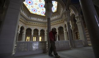 A worker walks trough the  Sarajevo National Library Friday, April 11, 2014. Workers are rushing to finish the reconstruction of the National Library - a landmark destroyed during the Bosnian war - in time for the ceremonies marking the centenary of the assassination in the city that ignited World War I.  The 19th century pseudo-Moorish-style building was completely destroyed by Serb shelling in 1992, along with its almost 2 million books and manuscripts. Reconstruction has taken 18 years at the cost of over 16 million euro, over a half of it provided by the European Union. (AP Photo/Amel Emric)