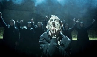 """In this undated handout photo provided by the Almeida Theatre on Friday, April 11, 2014, actress Katie Brayben is seen wearing a mask that depicts Britain's Prince Charles during a scene from the play 'King Charles III' at the Almeida Theatre in London. A new play about Britain's future king is getting rave reviews. Once it would have been theatrical treason. """"King Charles III"""" imagines current heir Prince Charles taking the throne, with catastrophic results. Just a few decades ago, depictions of living British monarchs were banned from the country's stages. (AP Photo/Almeida Theatre, Johan Persson) NO ARCHIVE"""
