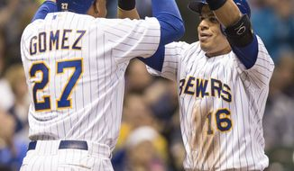 Milwaukee Brewers' Aramis Ramirez gets a high-five from teammate Carlos Gomez after hitting a two-run home run off Pittsburgh Pirates' Francisco Liriano during the fourth inning of a baseball game on Friday, April 11, 2014, in Milwaukee. (AP Photo/Tom Lynn)