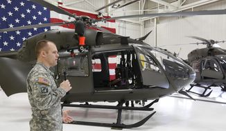 Mike Mauss a helicopter instructor pilot describes the differences between the two new UH-72A Lakota helicopters to the media at the Iowa Army National Guard Air Aviation Support Facility Thursday, April 10, 2014, in Waterloo, Iowa.  (AP Photo/Waterloo Courier, Matthew Putney)