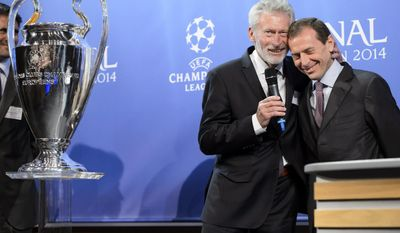 FC Bayern Muenchen club ambassador Paul Breitner, left, cheers with Real Madrid C.F. institutional Relations Director Emilio Butragueno, left, after the draw of the semi-finals of UEFA Champions League 2013/14 at the UEFA Headquarters in Nyon, Switzerland, Friday, April 11, 2014. (AP Photo/Keystone/Laurent Gillieron)