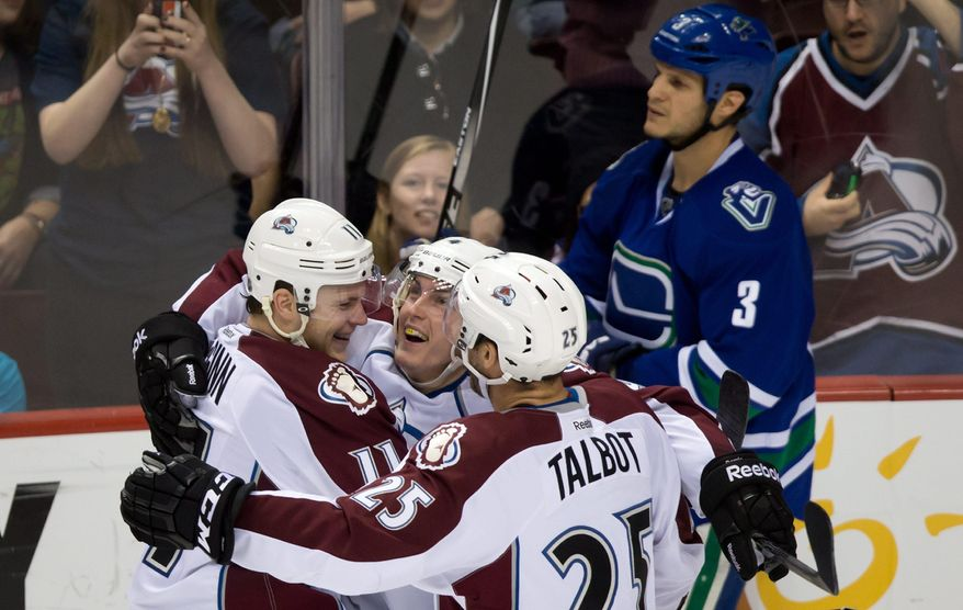 Colorado Avalanche's Jamie McGinn, Tyson Barrie and Maxime Talbot. from left, celebrate Barrie's goal as Vancouver Canucks' Kevin Bieksa skates past during the third period of an NHL hockey game Thursday, April 10, 2014, in Vancouver, British Columbia. (AP Photo/The Canadian Press, Darryl Dyck)