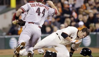 San Francisco Giants' Buster Posey (28) reaches first base safely on a bunt-single as he becomes entangled with Arizona Diamondbacks first baseman Paul Goldschmidt, left, during the third inning of a baseball game on Thursday, April 10, 2014, in San Francisco. Posey drove in a run with the single. (AP Photo/Marcio Jose Sanchez)