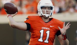 FILE - In this Sept. 1, 2012 file photo, Oklahoma State quarterback Wes Lunt throws against Savannah State during an NCAA college football game in Stillwater, Okla. Illinois head coach Tim Beckman says he's in no hurry to name a starting quarterback and that the competition between the three potential candidates to succeed Nathan Scheelhaase is wide open. Lunt brings a skill set and a pedigree that the Illini haven't seen in a while. The tall, strong-armed quarterback sat out last season after transferring from Oklahoma State. (AP Photo/Sue Ogrocki, File)