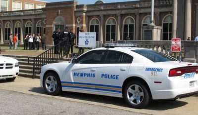 A police car is parked outside East High School during a lockdown of the school Friday, April 11, 2014, in Memphis, Tenn. Police searched the school after a report of four armed people inside the building, but no intruders were found, authorities said. (AP Photo/Adrian Sainz)