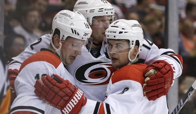 Carolina Hurricanes left wing Jiri Tlusty, left, of the Czech Republic, is congratulated on his goal by teammates Eric Staal, center, and Andrei Loktionov, right, of Russia during the first period of an NHL hockey game against the Detroit Red Wings in Detroit, Friday, April 11, 2014. (AP Photo/Carlos Osorio)