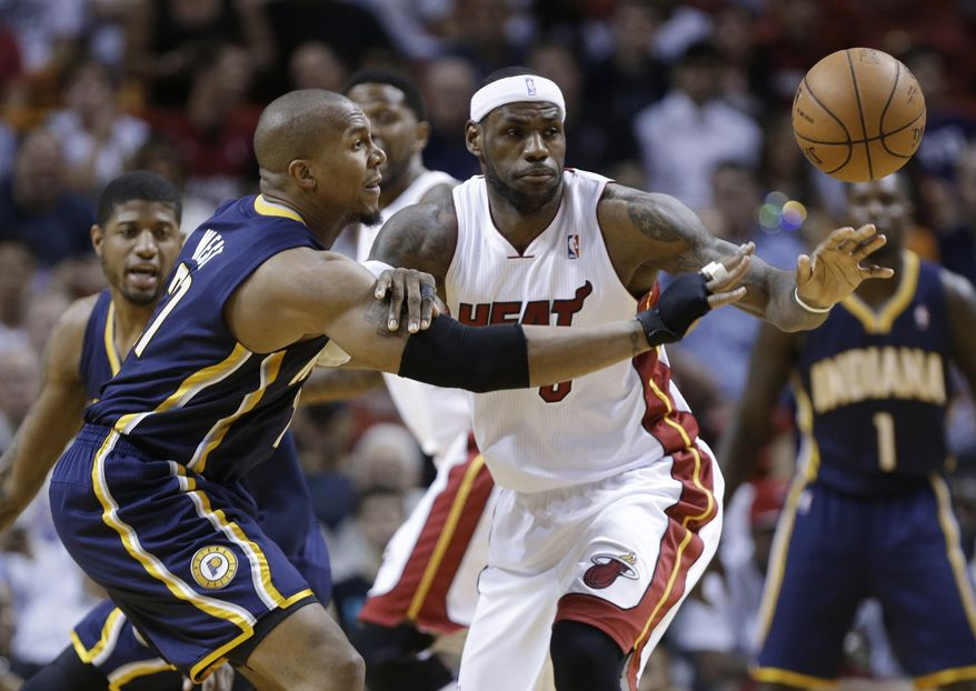 Miami Heat's LeBron James, middle, and Indiana Pacers' David West (21) watch the ball get away during the first half of an NBA basketball game, Friday, April 11, 2014, in Miami. (AP Photo/Lynne Sladky)