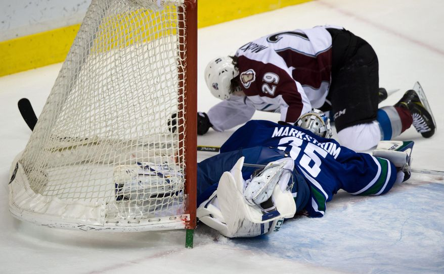 Vancouver Canucks goalie Jacob Markstrom, bottom, of Sweden, covers up the puck as Colorado Avalanche's Nathan MacKinnon crashes into the net during the second period of an NHL hockey game Thursday, April 10, 2014, in Vancouver, British Columbia. (AP Photo/The Canadian Press, Darryl Dyck)