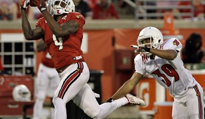 Louisville's senior wide receiver DeVante Parker (9) makes this catch after getting past defender Jordan Streeter (39) in their NCAA college spring football game in Louisville, Ky., Friday, April 11, 2014.  (AP Photo/Garry Jones)