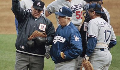 FILE - In this Oct. 8, 1988 file photo, umpire crew chief Harry Wendelstedt, left, signals the ejection of Los Angeles Dodgers pitcher Jay Howell, rear right, after a possible illegal substance was found in Howell's glove in the eighth inning of  a playoff game, in New York. Dodgers manager Tom Lasorda, foreground center, talks to Wendelstedt. The rest of the players are unidentified. Howell was suspended for two games during the 1988 NL championship series against the New York Mets after he was found to have pine tar on his glove.(AP Photo/Bill Kostroun, File)