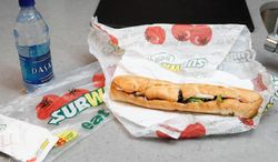 "FILE - This Aug. 11, 2009, file photo, shows a chicken breast sandwich and water from Subway on a kitchen counter in New York. Subway says an ingredient dubbed the ""yoga mat"" chemical will be entirely phased out of its bread by the week of April 14, 2014. The disclosure comes as Subway has suffered from an onslaught of bad publicity since a food blogger petitioned the chain to remove the ingredient. (AP Photo/Seth Wenig, File)"