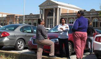 Concerned parents wait outside East High School during a lockdown of the school on Friday, April 11, 2014, in Memphis, Tenn. Police searched the school after a report of four armed people inside the building, but no intruders were found, authorities said. (AP Photo/Adrian Sainz)