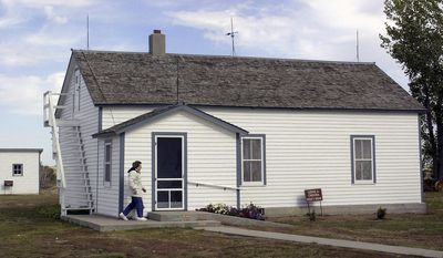 FILE - In this Oct. 10, 2002 file photo, Edna Schwab walks toward the front door of Lawrence Welk's boyhood home in Strasburg, N.D. The North Dakota State Historical Society is meeting Friday, April 11, 2014, in Bismarck, N.D. to get an update on its purchase of the famous band leader's home. The group voted 6-5 in January to buy the Strasburg homestead from Welk's nieces, but a final sale price was not negotiated. (AP Photo/Will Kincaid, File)