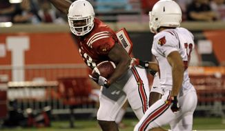 Louisville's Gerald Christian, left, makes a catch off balance in front of defender Jordan Streeter, right, in their NCAA college spring football game in Louisville, Ky., Friday, April 11, 2014.  (AP Photo/Garry Jones)