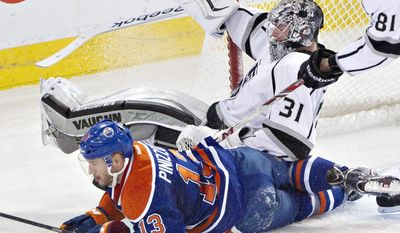 Los Angeles Kings goalie Martin Jones (31) is crashed into by Edmonton Oilers' Steven Pinizzotto (13) during second-period NHL hockey game action in Edmonton, Alberta, Thursday, April 10, 2014. (AP Photo/The Canadian Press, Jason Franson)