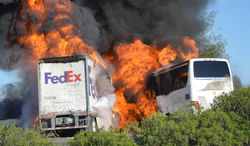 Massive flames are seen devouring both vehicles just after the crash, and clouds of smoke billowed into the sky  Thursday April 10, 2014 until firefighters had quenched the fire, leaving behind scorched black hulks of metal. The FedEx tractor-trailer crossed a grassy freeway median in Northern California and slammed into the bus carrying high school students on a visit to a college. At least nine were killed in the fiery crash, authorities said. (AP Photo/Jeremy Lockett)
