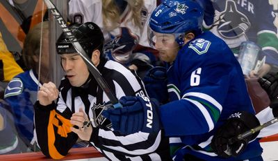 Vancouver Canucks' Yannick Weber, right, of Switzerland, runs into referee Ian Walsh during the third period of an NHL hockey game against the Colorado Avalanche on Thursday, April 10, 2014, in Vancouver, British Columbia. (AP Photo/The Canadian Press, Darryl Dyck)