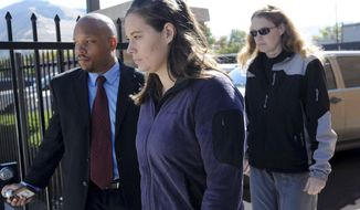 FILE - In this Oct. 4, 2013, file photo, Jordan Linn Graham, center, leaves federal court, in Missoula, Mont. Graham, who pleaded guilty to pushing her husband off a cliff in Glacier National Park last summer plans to appeal her 30-year prison sentence for his death. (AP Photo/The Missoulian, Michael Gallacher, File) TV OUT; MAGS OUT