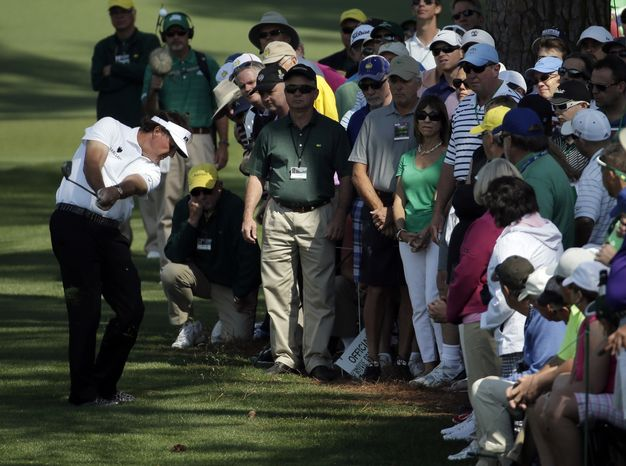 Spectators watch as Phil Mickelson hits out of the rough on the second fairway during the second round of the Masters golf tournament Friday, April 11, 2014, in Augusta, Ga. (AP Photo/Chris Carls