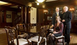 In this photo taken on April 1, 2104, Dallas Jones, left, and his wife Tish Gade-Jones pose for a portrait with their friend Jack Saltzman at the antique, custom-made African mahogany dining table in the formal dining room of the historic home of John and Christina Yost at 1900 South 25th Street. in Linconl, Neb. The home is now owned and occupied by Jones and his family, who are restoring parts of it to its original setting. The table, chairs and several accessories were purchased from the home by Saltzman in 1976 and resold to the Jones family in 2014. (AP Photo/The Journal-Star, Kristin Streff) LOCAL TV OUT; KOLN-TV OUT; KGIN-TV OUT; KLKN-TV OUT