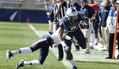 Connecticut blue team's Kamal Abrams is pushed out of bounds by white's Javon Hadley during the first half of UConn's Blue-White spring NCAA college football game at Rentschler Field, Saturday, April 12, 2014, in East Hartford, Conn. (AP Photo/Jessica Hill)