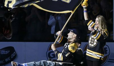 """FILE - In this June 19, 2013 file photo, Boston Marathon bombing victim Marc Fucarile waves a """"Boston Strong"""" flag with his fiancee, Jen Regan, and their son, Gavin, partially obscured, before Game 4 of the NHL hockey Stanley Cup Finals between the Boston Bruins and the Chicago Blackhawks in Boston. (AP Photo/Elise Amendola)"""