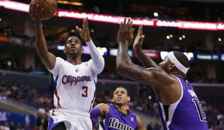 Los Angeles Clippers guard Chris Paul shoots the ball in front of Sacramento Kings guard Ray McCallum, center, and Kings center DeMarcus Cousins, right, during the first half of an NBA basketball game in Los Angeles, Sunday, April 12, 2014. (AP Photo/Danny Moloshok)