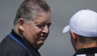 Kansas coach Charlie Weis talks with a referee before an NCAA college football spring game in Lawrence, Kan., Saturday, April 12, 2014. (AP Photo/Orlin Wagner)