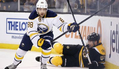 Buffalo Sabres' Cory Conacher (88) skates away after checking Boston Bruins' Johnny Boychuk (55) into the boards during the first period of an NHL hockey game in Boston, Saturday, April 12, 2014. (AP Photo/Michael Dwyer)