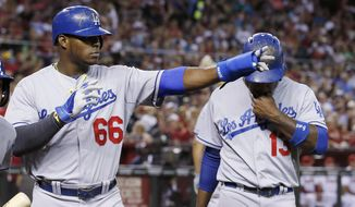 Los Angeles Dodgers' Yasiel Puig (66) points to teammate Adrian Gonzalez, who singled in Puig and Hanley Ramirez, right, during the third inning of a baseball game against the Arizona Diamondbacks on Friday, April 11, 2014, in Phoenix. The Dodgers won 6-0. (AP Photo/Ross D. Franklin)