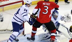Ottawa Senators' Marc Methot (3) and Toronto Maple Leafs' Peter Holland (24) look on as the puck gets behind Maple Leafs goaltender James Reimer during first-period NHL hockey game action in Ottawa, Ontario, Saturday, April 12, 2014. There was no goal scored on the play. (AP Photo/The Canadian Press, Fred Chartrand)