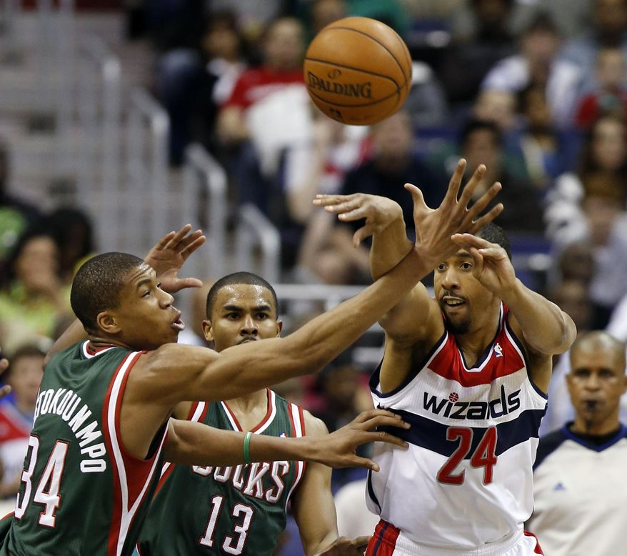 Washington Wizards guard Andre Miller (24) passes past Milwaukee Bucks guards Giannis Antetokounmpo (34), from Greece, and Ramon Sessions (13) in the first half of an NBA basketball game, Saturday, April 12, 2014, in Washington. (AP Photo/Alex Brandon)