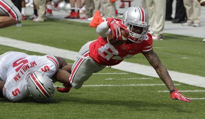 Ohio State wide receiver Corey Smith, right, tries to escape the tackle of linebacker Raekwon McMillan during their spring NCAA college football game Saturday, April 12, 2014, in Columbus, Ohio. (AP Photo/Jay LaPrete)