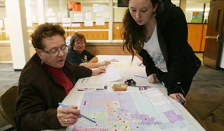 ADVANCE FOR RELEASE SATURDAY, APRIL 12, 2014, AND THEREAFTER- In this April 8, 2014 photo, Donna Dill, left, of the League of Women Voters, and Hastings High senior Destiny Thomas examine a map of Hastings to find Thomas' voting precinct after she registered to vote at the school in Hastings, Neb. (AP Photo/The Hastings Tribune, Amy Roh)