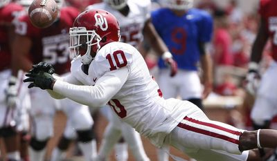 Oklahoma safety Quentin Hayes (10) misses a pass from quarterback Trevor Knight (9) during their annual spring NCAA college football game in Norman, Okla., Saturday, April 12, 2014. (AP Photo/Alonzo Adams)