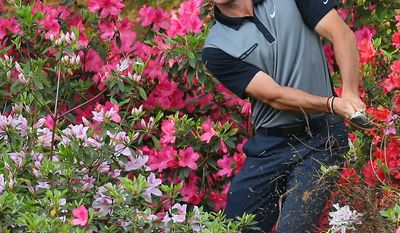 Rory McIlroy, of Northern Ireland, hits from the azaleas on No. 13 during the second round of the Masters golf tournament, Friday, April 11, 2014, in Augusta, Ga. (AP Photo/Atlanta Journal Constitution, Curtis Compton) MARIETTA DAILY OUT; GWINNETT DAILY POST OUT; WXIA OUT; WGCL OUT; FOX 5 OUT