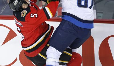 Winnipeg Jets' Michael Frolik, right, from Czech Republic, collides with Calgary Flames' Mark Giordano during first period NHL action in Calgary, Alberta, Friday, April 11, 2014.  (AP Photo/The Canadian Press, Larry MacDougal)