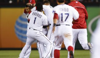 Texas Rangers' Robinson Chirinos is swarmed by teammates after hitting a game-ending single that scored Kevin Kouzmanoff against the Houston Astros during the 12th inning of a baseball game, Friday, April 11, 2014, in Arlington, Texas. The Rangers won 1-0. (AP Photo/Jim Cowsert)