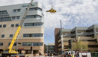 In this photo provided by the University of New Mexico Hospital, a medical helicopter is removed from the roof of University of New Mexico Hospital on Saturday, April 12, 2014 in Albuquerque, N.M.  UNM spokesman Billy Sparks says the hospital remained fully operational during the process. Sparks says the hospital temporarily converted to using power from an internal generator, eliminating the potential for any accidents ignited by outside power sources. Sparks says a tail section was the first piece removed followed by jet fuel, which was channeled into special hazmat barrels, and then the helicopter's body. Officials are hoping to begin construction repairs to the roof by Saturday night. The helicopter crashed on Wednesday.  (AP Photo/University of New Mexico Hospital courtesy of John Arnold)