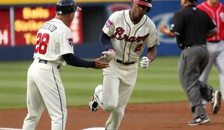 Atlanta Braves' B.J. Upton (2) celebrates his solo home run off Washington Nationals starting pitcher Taylor Jordan with third base coach Doug Dascenzo (28) in the first inning of a baseball game on Saturday, April 12, 2014, in Atlanta. (AP Photo/Jason Getz)