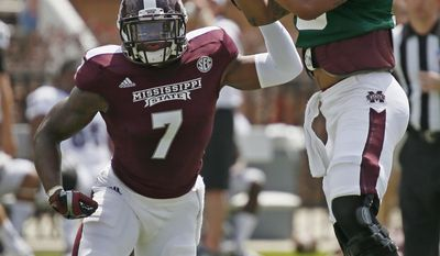 CORRECTS YEAR - Mississippi State Maroon quarterback Dak Prescott (15) pulls down a high snap for running back Nick Griffin (7) during the first half of their spring NCAA college football game against the White squad, Saturday, April 12, 2014, in Starkville, Miss. Maroon won 41-38. (AP Photo/Rogelio V. Solis)