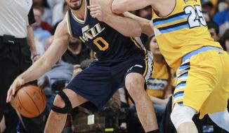 Utah Jazz center Enes Kanter, left, of Turkey, works ball inside as Denver Nuggets center Timofey Mozgov, of Russia, covers in the first quarter of an NBA basketball game in Denver on Saturday, April 12, 2014. (AP Photo/David Zalubowski)