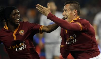 Roma's Rodrigo Taddei, right, celebrates with teammate Gervinho after scoring during a Serie A soccer match between Roma and Atalanta in Rome's Olympic stadium, Saturday, April 12, 2014. (AP Photo/Gregorio Borgia)