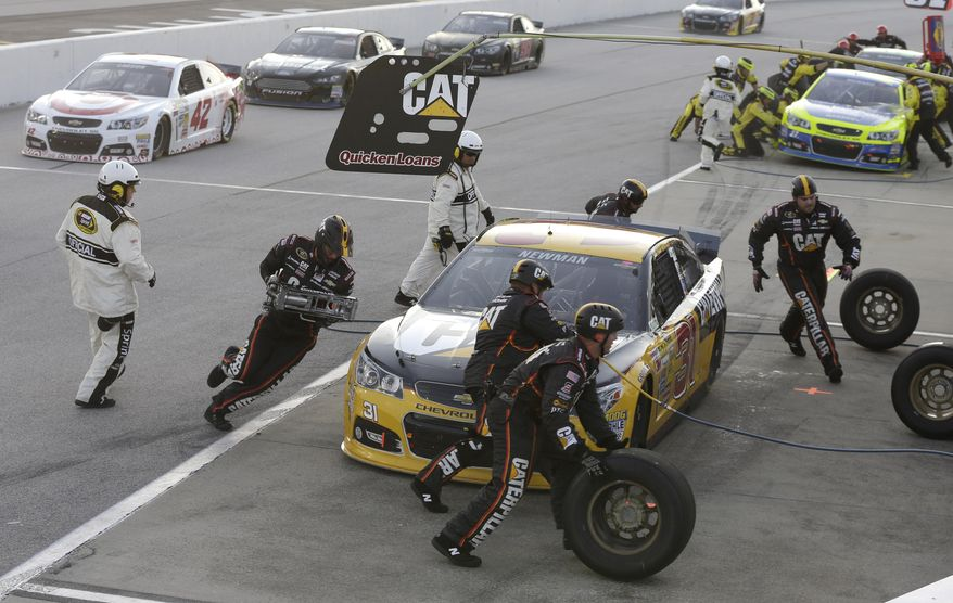 Ryan Newman's crew works on his car during a pit stop in the NASCAR Sprint Cup auto race at Darlington Speedway in Darlington, S.C., Saturday, April 12, 2014. (AP Photo/Chuck Burton)