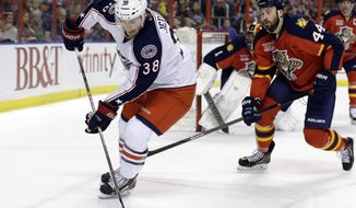 Columbus Blue Jackets center Boone Jenner (38) skates with the puck as Florida Panthers defenseman Erik Gudbranson (44) pursues in the first period of a hockey game, Saturday, April 12, 2014, in Sunrise, Fla. (AP Photo/Lynne Sladky)