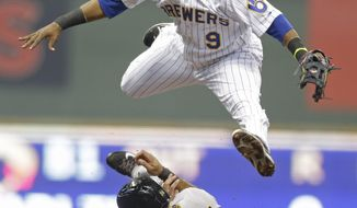 Milwaukee Brewers' Jean Segura (9) forces out Pittsburgh Pirates' Pedro Alvarez at second base and throws on to first for a double play on Russell Martin during the first inning of a baseball game Saturday, April 12, 2014, in Milwaukee. (AP Photo/Jeffrey Phelps)